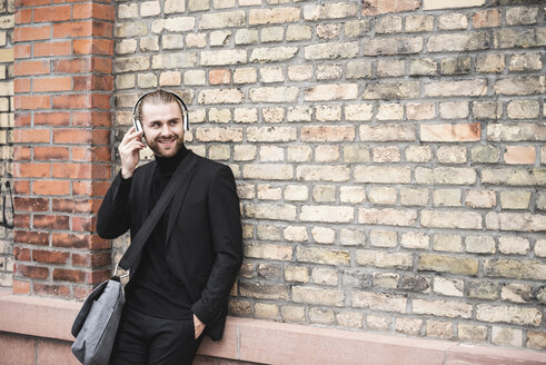 Smiling fashionable young man with headphones leaning against brick wall - UUF15300