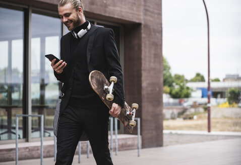 Smiling fashionable young man holding cell phone and skateboard passing office building - UUF15303