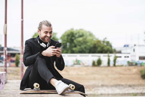 Smiling fashionable young man sitting outdoors with cell phone and skateboard - UUF15306