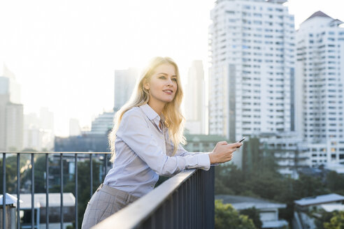 Blonde smiling business woman leaning onto handrail holding smartphone on city rooftop - SBOF01506