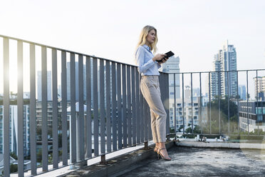 Blonde business woman leaning onto handrail holding tablet on city rooftop - SBOF01509