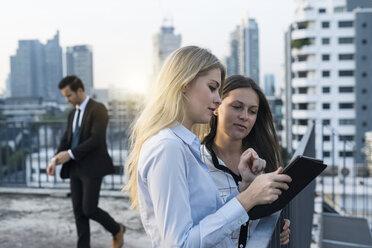 Two businesswomen talking on city rooftop, using digital tablet - SBOF01512