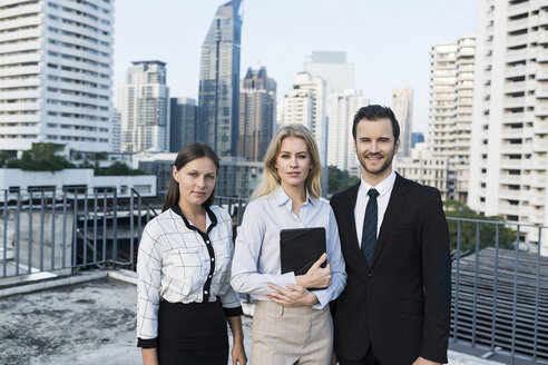 Group of successful business people on city rooftop, holding digital tablet - SBOF01515