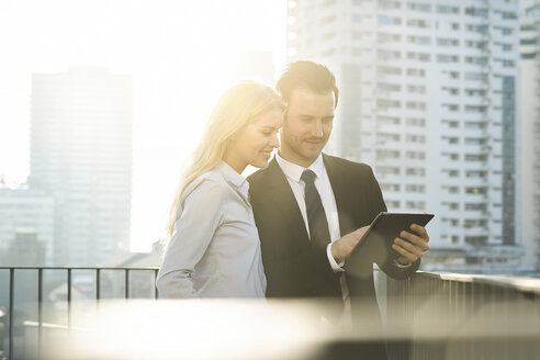 Blonde businesswoman and male colleague using digital tablet on city rooftop - SBOF01527