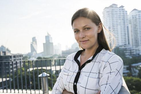 Portrait of brunette business woman on rooftop - SBOF01530