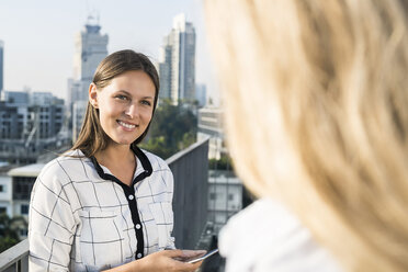 Two female colleagues speaking with each other on city rooftop - SBOF01533