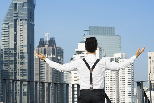 Happy and content successful business man on city rooftop - SBOF01539