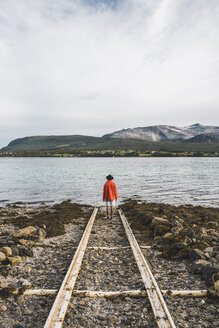 Northern Norway, Man standing alone at fjord, looking at view - KKAF02030