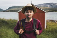Young man with backpack exploring red barn in Northern Norway - KKAF02036