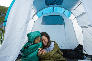 Friends camping in a tent, having fun looking at their smartphone - KKAF02075