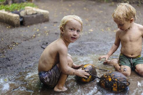 Two boys playing in mud, Nusa Penida, Bali, Indonesia - AURF07351