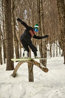 Snowboarder sliding on wooden feature in terrain park, Vermont, USA - AURF07440