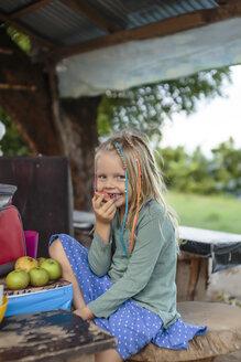 Smiling girl eating apple, Nusa Penida, Bali, Indonesia - AURF07497