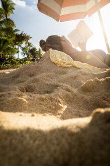 Woman in bikini reading book on beach, Oahu, Hawaii, USA - AURF07593