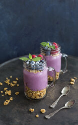 Two glasses of yoghurt with peanut granola, aronia powder and topping of chopped hazelnuts and frozen berries - JUNF01307