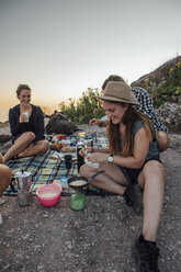 Switzerland, Grosser Mythen, happy girlfriends on a hiking trip having a picnic break at sunrise - LHPF00045
