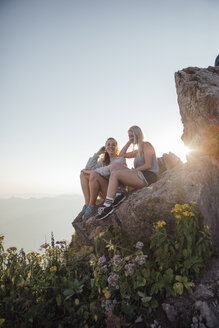 Switzerland, Grosser Mythen, two happy girlfriends on a hiking trip having a break at sunrise - LHPF00051