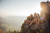 Switzerland, Grosser Mythen, four happy girlfriends on a hiking trip having a break at sunrise - LHPF00057