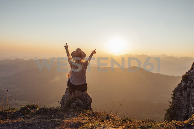 Switzerland, Grosser Mythen, young woman on a hiking trip sitting on a rock at sunrise - LHPF00060 - letizia haessig photography/Westend61