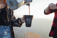 Close-up of woman on a hiking trip at sunrise pouring coffee into a cup for a friend - LHPF00069