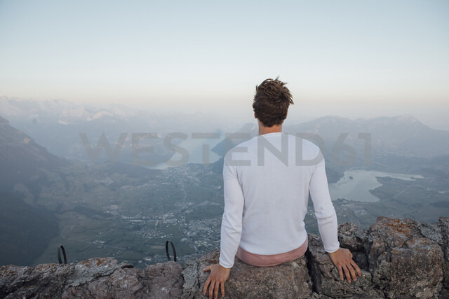 Switzerland, Grosser Mythen, young man on a hiking trip sitting on a rock at sunrise - LHPF00072