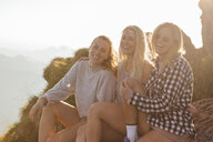 Switzerland, Grosser Mythen, three happy girlfriends on a hiking trip having a break at sunrise - LHPF00075