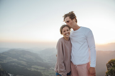 Switzerland, Grosser Mythen, portrait of happy young couple standing in mountainscape at sunrise - LHPF00078