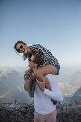 Switzerland, Grosser Mythen, happy young man carrying girlfriend piggyback - LHPF00087