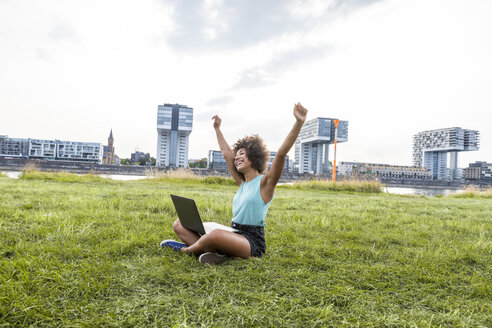 Germany, Cologne, cheering woman sitting on a meadow using laptop - FMKF05254