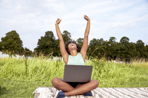 Cheering woman sitting on blanket in a meadow using laptop - FMKF05257