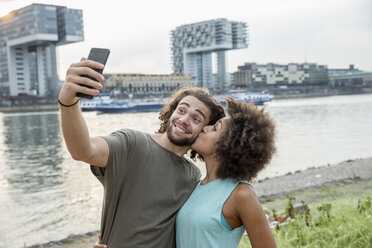 Germany, Cologne, happy couple taking a selfie at the riverside - FMKF05275