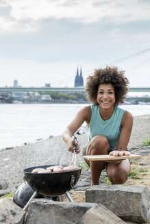 Germany, Cologne, portrait of smiling woman having a barbecue at the riverside - FMKF05278