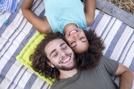 Happy couple with closed eyes lying on a blanket outdoors - FMKF05284