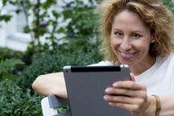 Portrait of smiling woman using digital tablet - HHLMF00494