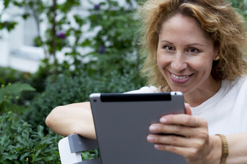 Portrait of smiling woman using digital tablet - HHLMF00494