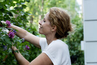Profile of smiling woman gardening - HHLMF00497
