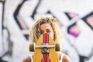 Portrait of young woman with skateboard at graffiti wall - WPEF00782
