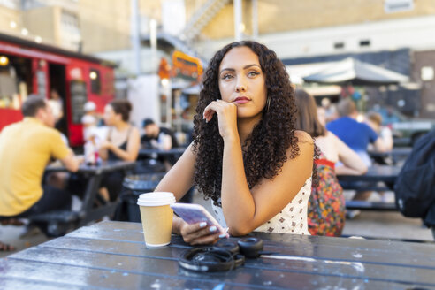 Beautiful young woman with cell phone sitting at a table and waiting - WPEF00797