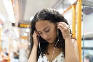 Young woman listening to music with earphones on the subway train - WPEF00803