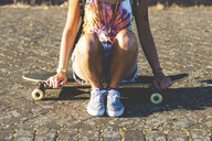 Close-up of young woman sitting on a skateboard in sunlight - WPEF00812