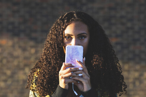 Portrait of young woman with curly hair holding cell phone - WPEF00815