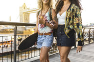 UK, London, two friends carrying a longboard with Tower Bridge in background at sunset - WPEF00824