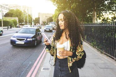 UK, London, young woman with cell phone on the pavement in the city - WPEF00827