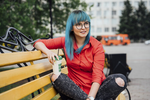 Portrait of young woman with dyed blue hair sitting on a bench with beverage - VPIF00829