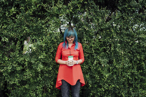 Young woman with dyed blue hair standing in front of a hedge with beverage - VPIF00832
