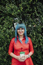 Portrait of young woman with dyed blue hair standing in front of a hedge with beverage - VPIF00835