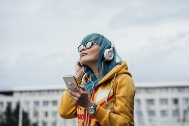 Portrait of young woman with dyed blue hair listening music with smartphone and headphones - VPIF00838
