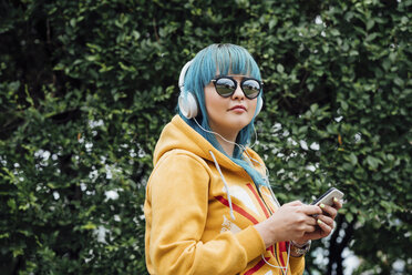 Portrait of young woman with dyed blue hair listening music with smartphone and headphones - VPIF00841