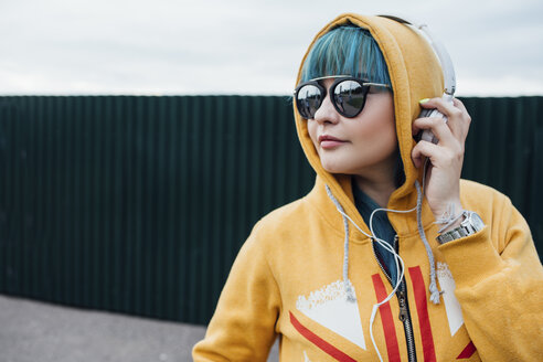 Portrait of young woman with dyed blue hair listening music with headphones - VPIF00844