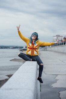 Portrait of young woman with dyed blue hair sitting on a wall showing victory signs - VPIF00853